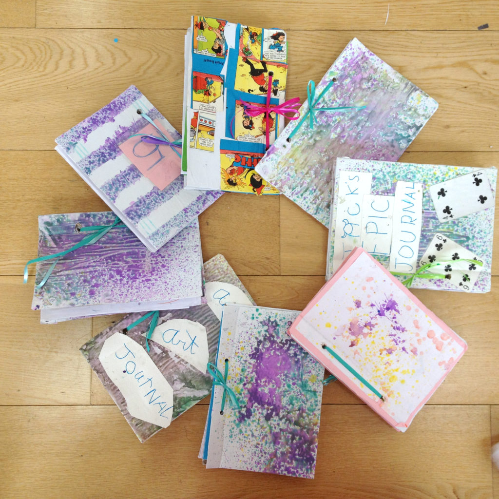 spray painting notebooks with kids at our summer camps