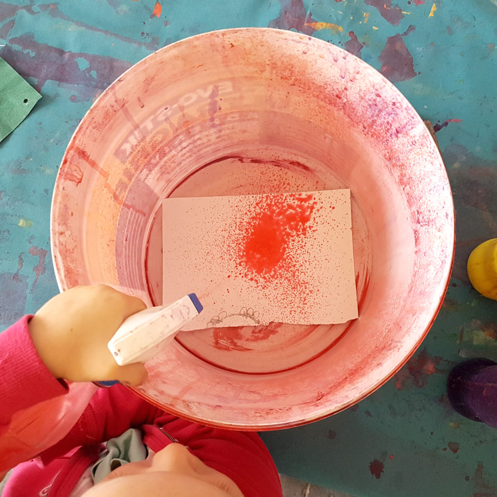 Spray painting with kids using an old plastic bucket
